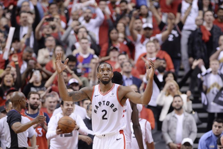 "Toronto Raptors forward Kawhi Leonard reacts following the Raptors win against the Milwaukee Bucks in Game 3 of the NBA Eastern Conference finals in Toronto on Sunday, May 19, 2019. Kawhi Leonard's likeness looks down from some 10 storeys high over Yonge-Dundas Square in the heart of downtown Toronto. Arms crossed. Serious face. The tagline reads: ""Fun Guy."" Leonard looks anything but. And that's the appeal."