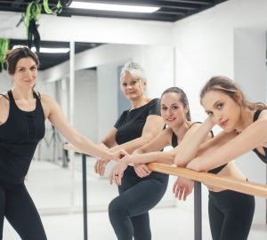 Group of women standing by the barre at pilates class and looking at camera.