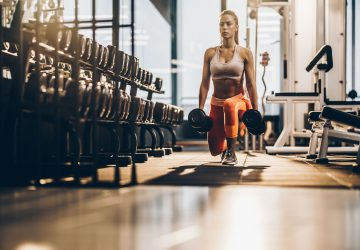 woman doing dumbell lunges in the gym