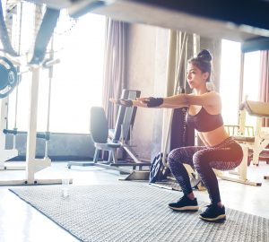Deep squat of young woman in sportswear doing squat while standing in front of glass at gym