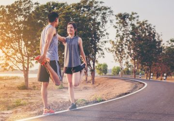 Young couples athletes worming up for outdoor practice with sunset background