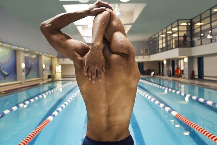 man stretching before going for a swim