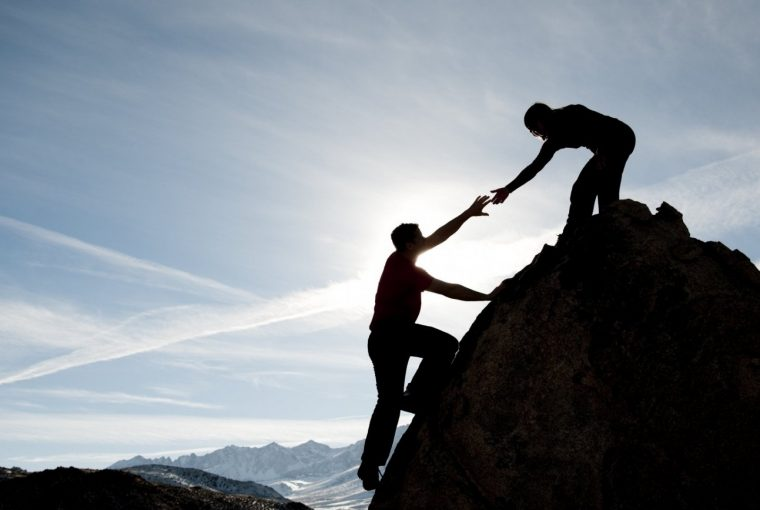 a man getting help up a mountain