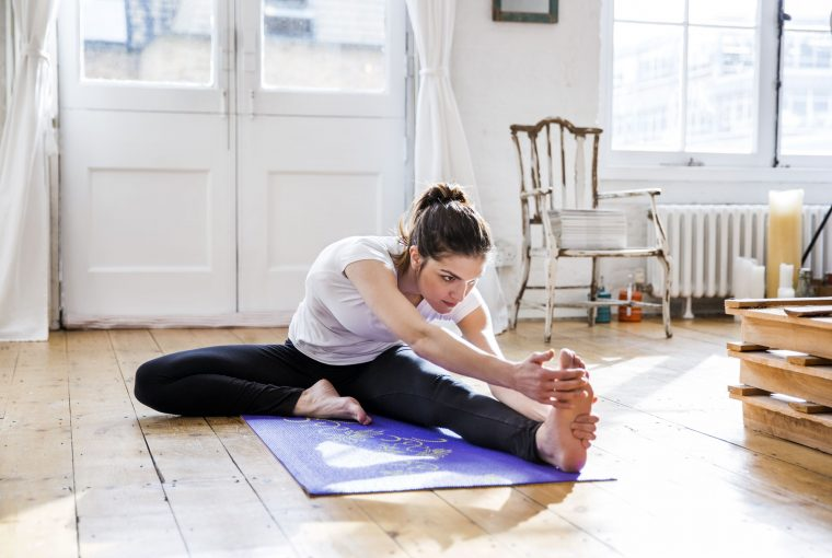 a woman stretching in her home