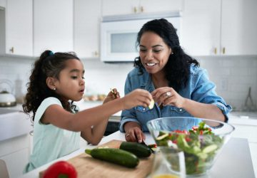 a mom and daughter eat a healthy meal